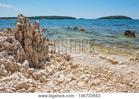 Rocky beach, bue sea and islands in Istria, Croatian coast