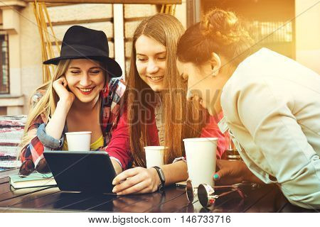 Group of girls sits in coffee house with tablet computer and having fun