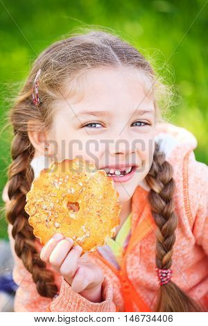 Sweet girl with a fallen tooth holding cookies in her hand on nature