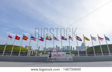 KALLANG SINGAPORE - MAY 30 2015 : A boy walks across the national flags of Southeast Asia countries; Brunei Darussalam Myanmar / Burma Cambodia Indonesia Laos Malaysia Philippines Singapore Thailand Vietnam East Timor.