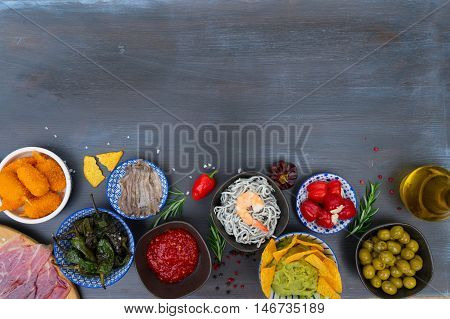 Table with spanish tapas - anchovies with peppers padron, jamon, croquetes, guacamole and olives, border with copy space, picnic table