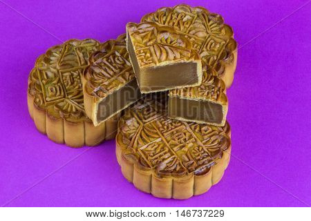 Whole and cut chinese mooncakes on a purple background