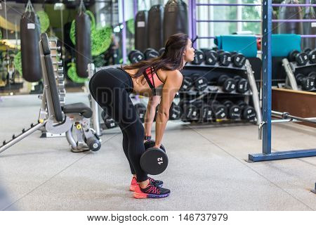 Fit woman performing weight lifting deadlift exercise with dumbbell at gym.