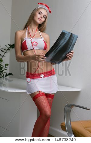 sexy blonde woman in seductive nurse costume with X-ray photo in hand