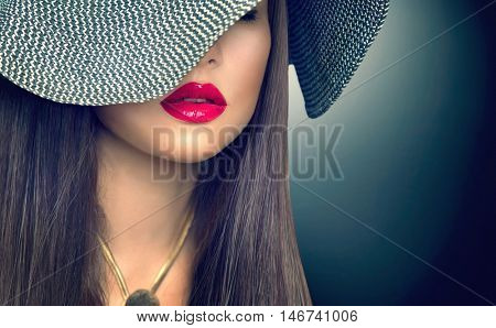 Beautiful sexy brunette woman with red lips in modern black hat. Beauty fashion model girl portrait with accessories- necklace and elegant hat over dark background. Romantic lady