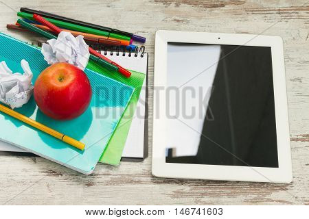 Apple with school supplies and tablet on white wooden table