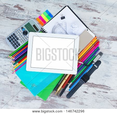 back to school frame with school supplies and electronic device tablet on wooden table, copy space on empty screen
