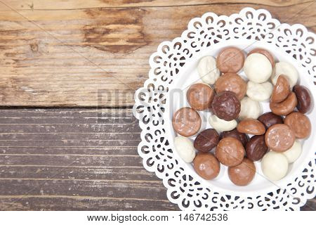 Dutch candy chocolate pepernoten on white plate on brown wooden background