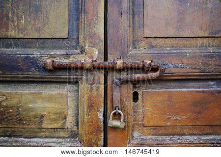 Metal door latch with padlock on an ancient wooden door