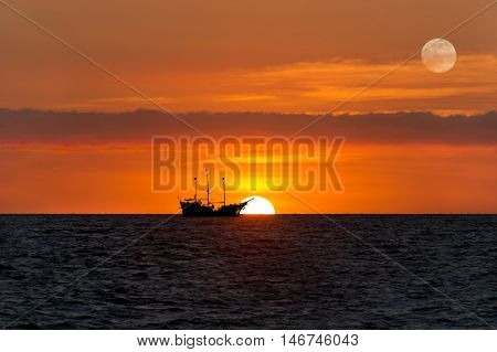 Pirate ship fantasy is an old wooden pirate ship with full flags as the sun sets on the ocean horizon in a colorful sunset sky.
