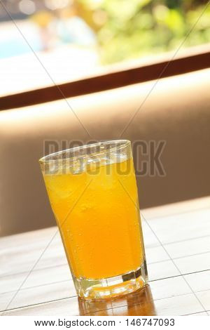 A glass of fizzy drink on a wooden table