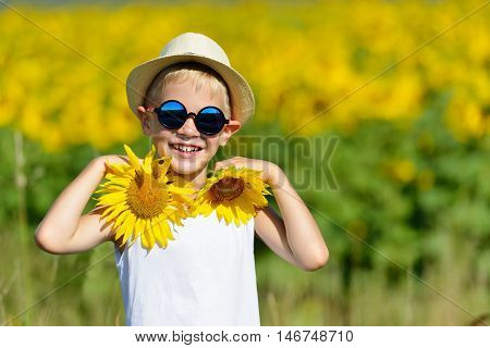 Cute Laughing Blond Boy In Sun Glasses And Hat With Sunflowers On Field Outdoors