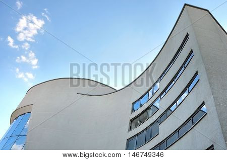 Grodno, Belarus - June 22, 2016: Facade of modern Philharmonic. Concert hall with curved walls and mirrored windows. Look up.