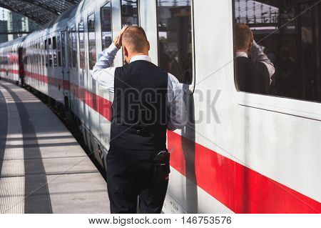 Berlin Germany - September 9 2016: Train conductor from behind standing in front of ice train at central staion in Berlin.