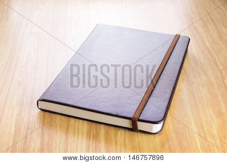 Brown Hard Cover Notebook With Elastic Strap On Wooden Table In Perspective View,template For Adding