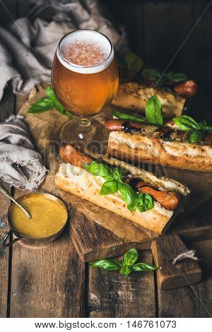 Glass of wheat unfiltered beer and grilled sausage dogs in baguette with mustard, caramelised onion and herbs on serving board over rustic wooden background, selective focus