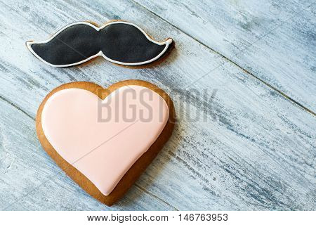 Heart shaped biscuit. Moustache cookie with black glaze. Gentleman sends greeting to lady. Feelings and manners.