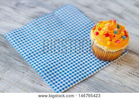 Cupcake on blue napkin. Icing of orange color. New dessert in bistro menu. Tasty food and good service.
