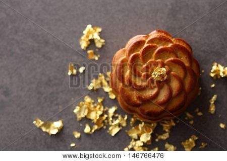 Luxury mooncake with gold topping on grey background