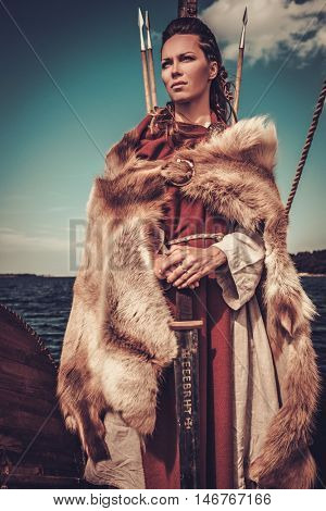 Confident viking woman with sword and shield standing on Drakkar.