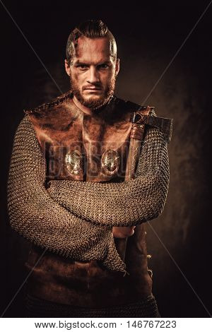 Serious viking in a traditional warrior clothes, posing on a dark background.