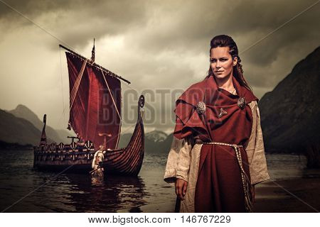 Confident viking woman with sword and shield standing near Drakkar on the seashore.
