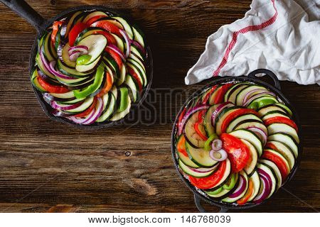 Vegetable ratatouille in iron cast skillet before oven on rustic wooden background. Healthy vegetarian food, dinner meal. Top view, horizontal