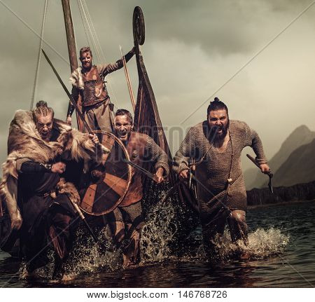 Vikings warriors in the attack, running along the shore with Drakkar on the background.