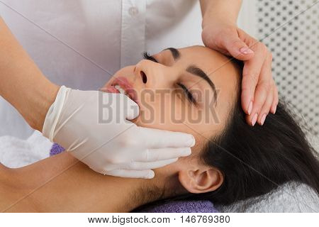 Intra oral neuromuscular massage in spa. Female doctor with patient in wellness center. Professional cosmetologist make procedure to beautiful indian girl in cosmetology cabinet or beauty parlor. poster