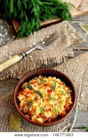 Risotto with vegetables in a bowl, fork, dill sprigs, cutting board on a wooden table. Rice cooked with tomatoes, garlic and carrots and garnished with dill. Top view