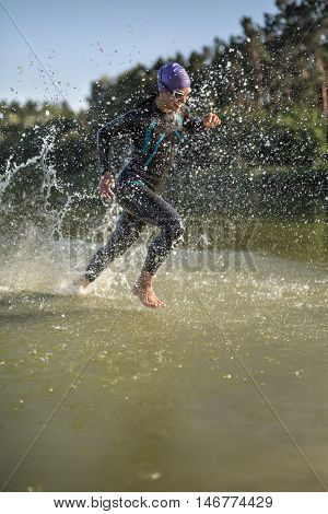 Energetic female runner runs on the water outdoors. She wears a dark swimrun suit, violet cap, swim glasses and a stopwatch. Water splashes are around her body. Sun shines at her body. Vertical.