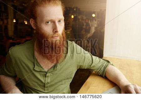 Young Photographer With Thick Red Beard And Stylish Haircut Retouching Pictures Using Notebook At Co