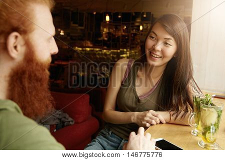 Young Attractive Asian Girl With Dark Hair Having Conversation With Redhead Stylish-looking Man, Lau
