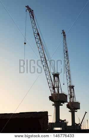 Silhouette of Cranes at Work in Boatyard and Blue Sky in background