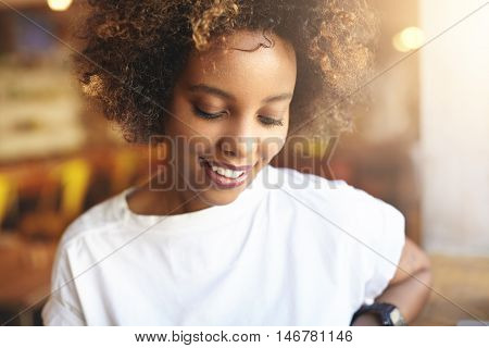 Close Up Of Good-looking African Woman With Curly Hair Dressed In White T-shirt, Spending Free Time