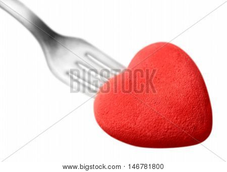 Macro studio image of stainless steel fork with red heart. Concept image for Valentine dinner/love food/love cooking etc. Differential focus with shallow DOF. Copy space