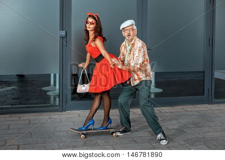 Woman riding on a skateboard her pushes the old man.