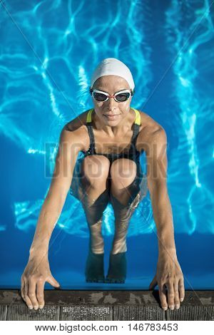 Nice swimmer in the swimming pool. Woman wears a black-lime swimsuit, a white swim cap and swim glasses. She looks into the camera and holds her hands on the pool side. Outdoors. Vertical.
