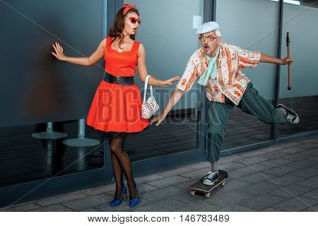 Funny old man races on a skateboard near young girl surprised.