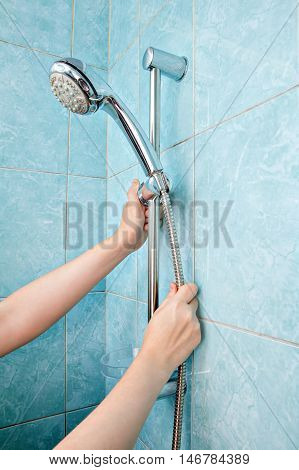 Replacing the plumbing in the bathroom close-up human hands installed hose with shower head in height adjustable shower bar slider rail.