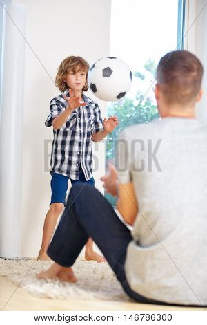 Happy father and son playing soccer at home in the living room