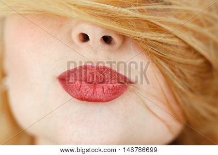 Red-haired woman pouting red lips with covered face. Beautiful girl sending kiss, close-up