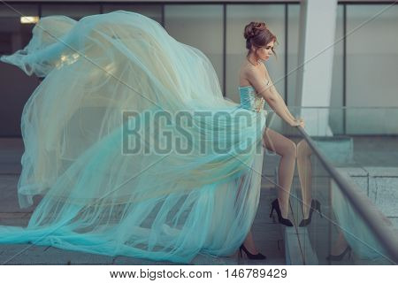 Beautiful girl standing on the balcony she was wearing a gentle blue dress that develops in the wind a very long dress.