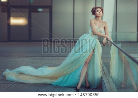 A young girl is she is dressed in a long dress is gentle blue.