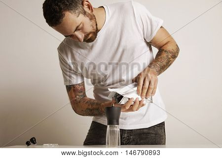 Bearded and tattooed man pouring coffee grounds into a modern manual coffee grinder from a white foiled bag poster