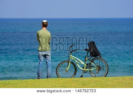 Lonely  jewish man standing on the sea shore, looking at the horizon and thinking.