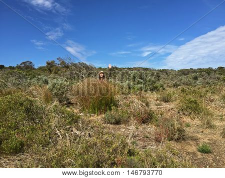 Asian woman with hat waving hand through tall grass and drought tolerant plants with blue sky background, Autumn in Australia