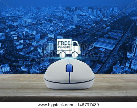 Wireless computer mouse with free delivery truck icon on wooden table over city tower street and expressway Transportation business concept