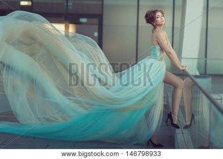 Young girl's dress gently blue color it flying in the wind.