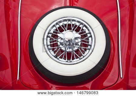 Chrome spare wheel on the trunk of a red car.